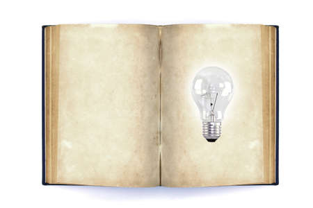 Old book and light bulb, isolated on white background photo
