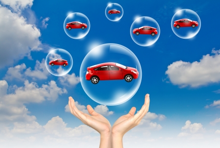 Hand hold Bubbles in the sky with car inside Stock Photo