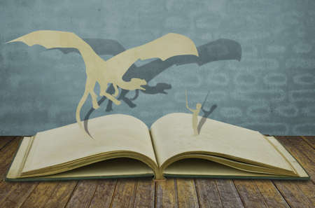 Paper cut of dragon and child hold sword on old book Stock Photo - 15093878