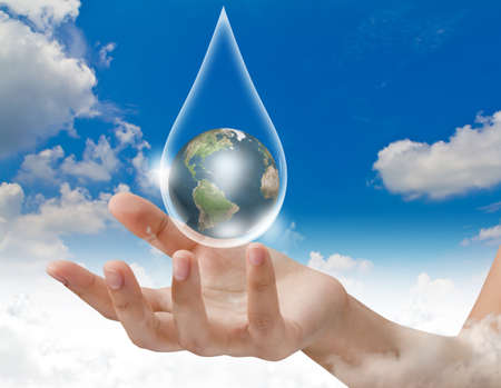 Eco concept : Hand with earth in water drop photo