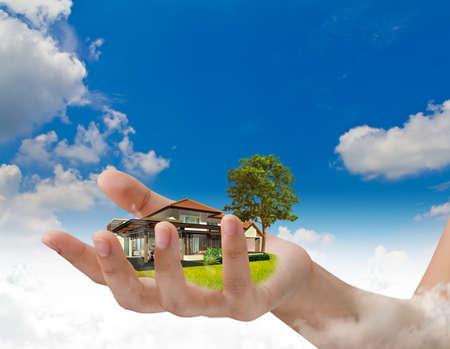 A ház az emberi kéz alatt kék ég Stock fotó