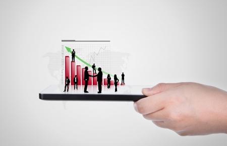 investment solutions: Mano que sostiene la moderna pc tableta digital con carta del �xito del crecimiento Foto de archivo