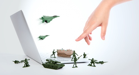Computer security concept :  soldiers,tank,plane  are guarding a laptop from viruses, spyware and hacker with hand Stock Photo - 15401367