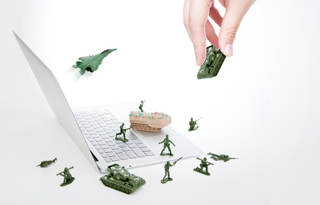 Computer security concept :  soldiers,tank,plane  are guarding a laptop from viruses, spyware and hacker with hand Stock Photo