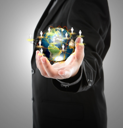 universal: Business man holding the small world in his hands against white background