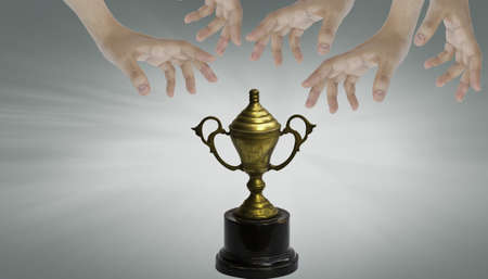Hands and old golden trophy photo