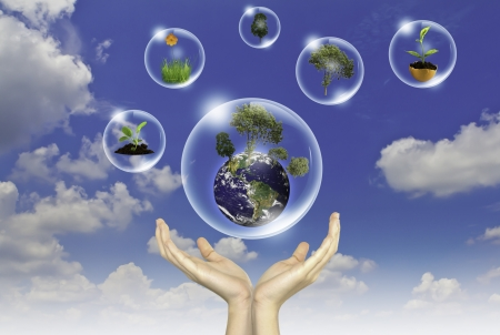 Eco concept : Hand hold earth ,tree and flower in bubbles against the sun and the blue sky photo