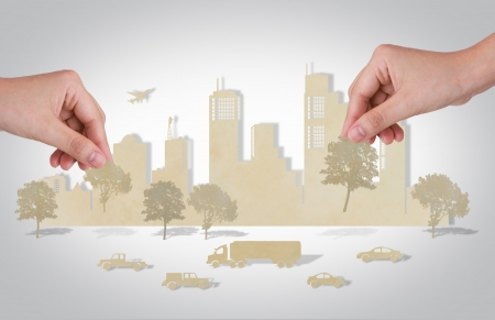 Woman hand holding tree over paper cut of cities with  car and plane photo