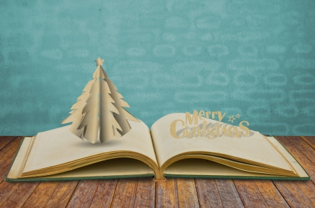 Paper cut of christmas tree on old book photo