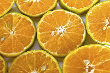 A glass of orange juice and sliced oranges on white background with copy space. photo