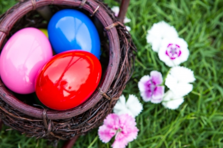 Basket of easter eggs on green grass photo