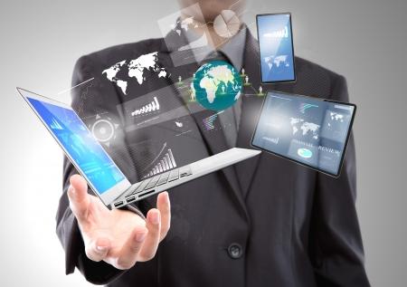 Biznesmen z laptopa, telefonu komórkowego, urządzenia z ekranem dotykowym