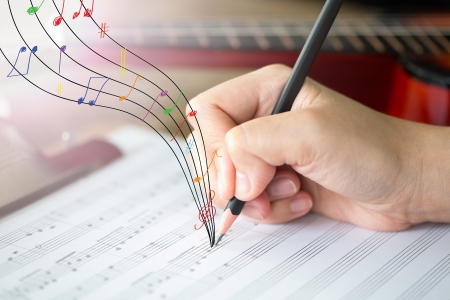 Hand with pencil and music sheet photo