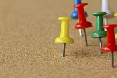noteboard: Group of colorful push pins on cork bulletin board.
