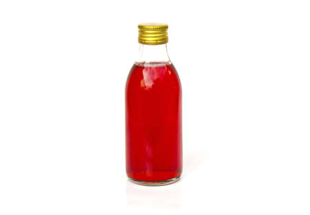 Close up on a medicine bottle with red syrup isolated on a white background. photo