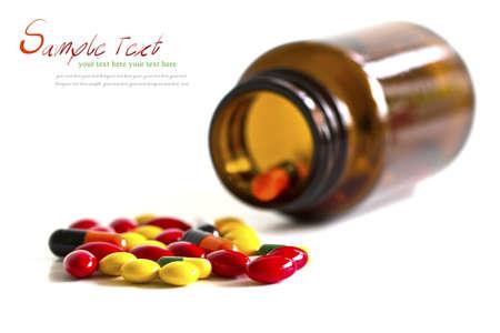 Pigułki, tabletki i kapsułki rozlane z butelki na białym tle z przestrzeni kopii. Zdjęcie Seryjne
