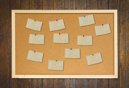 noteboard: cork bulletin board with old paper note on wood wall Stock Photo