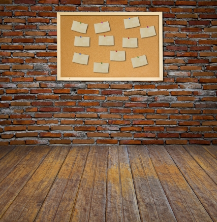 noteboard: Cork bulletin board with old paper note on brick wall.