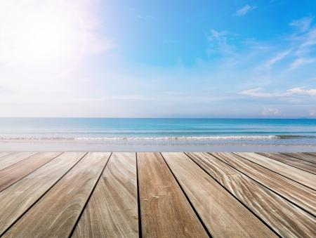 mesa de madera: terraza de madera en la playa y la luz del sol