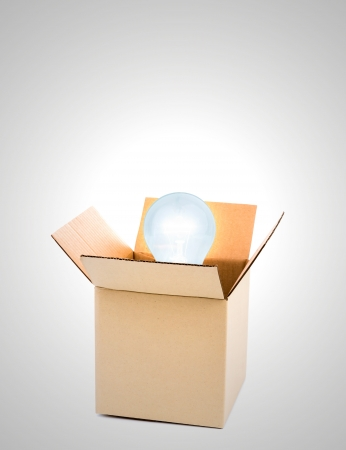 constraints: Glowing light bulb  over open cardboard box Stock Photo