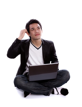 Portrait of young business man sitting using a laptop photo
