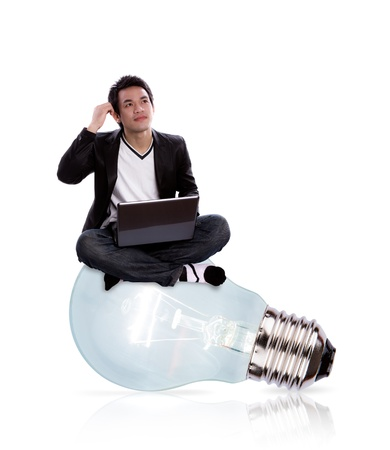 Portrait of business man  using laptop sitting on a big light bulb isolated on white background