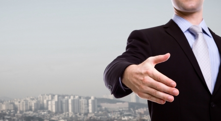 Portrait of young business man extending hand to shake over a cityscape photo