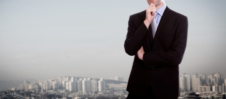 Businessman standing over a cityscape photo