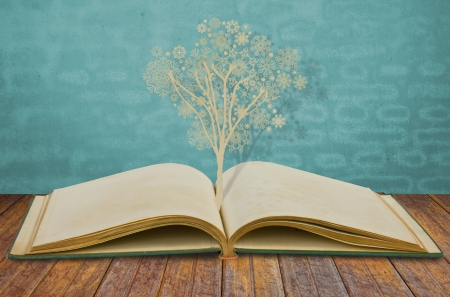 paper cut: Paper cut of christmas tree with snowflakes on old book Stock Photo