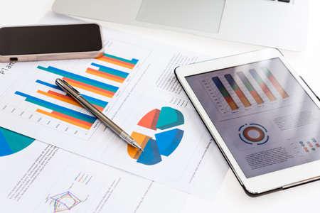 Wykresy finansowych w tabeli z tabletu i pióra