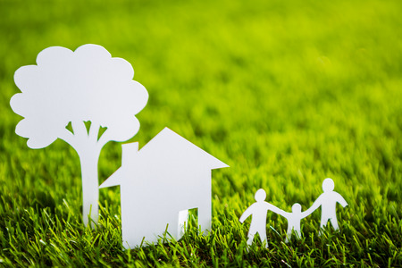clean house: Paper cut of family with house and tree on fresh spring green grass Stock Photo