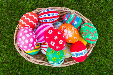 Basket of easter eggs on Fresh Green Grass photo