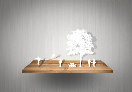 Paper cut of children play on wood shelf photo