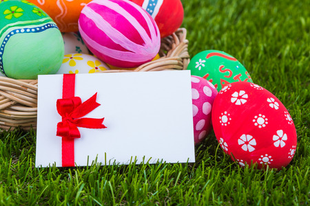 Basket of easter eggs with card on Fresh Green Grass photo