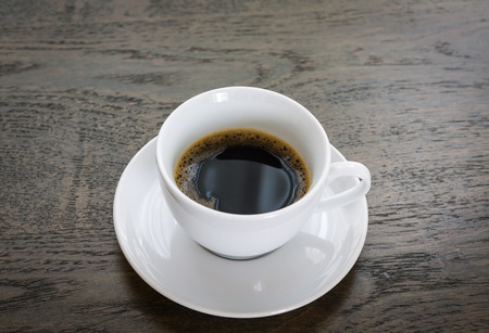 Coffee in white cup on wood table photo
