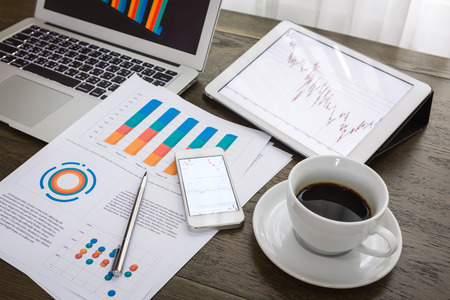 office desktop: Laptop, tablet, smartphone and coffee cup with financial documents on wooden table Stock Photo