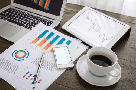 Laptop, tablet, smartphone en kopje koffie met financiële documenten op houten tafel Stockfoto