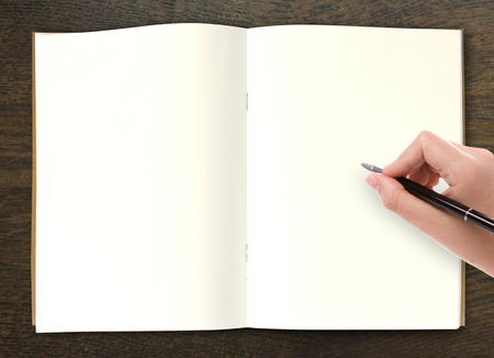Hand writing in open book on table photo