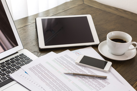 Laptop, tablet , smartphone and coffee cup with financial documents on wooden table photo