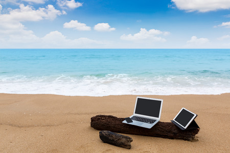 Laptop ,tablet  and smartphone on the beach in summer time photo