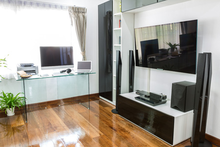 Modern office with computer and laptop with home theater photo