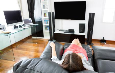 Biznes młoda kobieta oglądania telewizji w nowoczesnym domowym biurze z komputera i laptopa