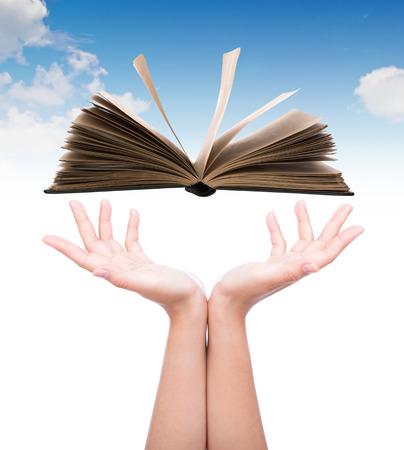 Women hand holding book over blue sky photo