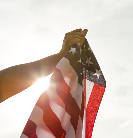 free vote: Hand hold American flag with sun light