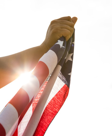 Hand hold American flag with sun light photo