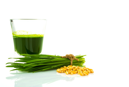Shot glass of wheat grass with fresh cut wheat grass and wheat grains Stock Photo