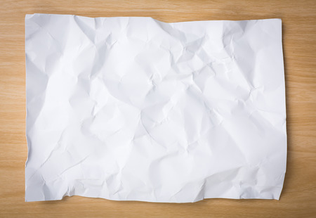 crumpled paper: White  crumpled paper on a wooden desk