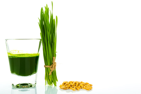 cut grass: Shot glass of wheat grass with fresh cut wheat grass and wheat grains Stock Photo