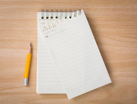 木製の机の上の鉛筆とメモ帳
