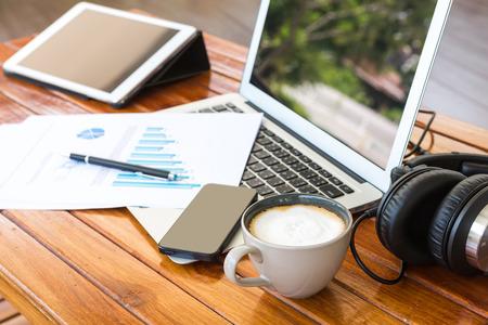 木製のテーブル上の金融ドキュメントとラップトップ、タブレット、スマート フォン、コーヒー カップ